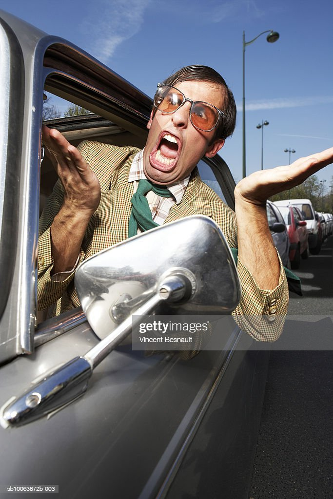driver looking out car window and yelling stock photo