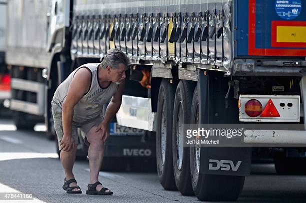 A driver looks looks underneath a lorry as migrants continue to try and board lorries bound for the United Kingdom on June 25 2015 in Calais France...