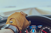 Man hand in leather glove on steering wheel inside a luxury car on highway with gps navigation on dashboard