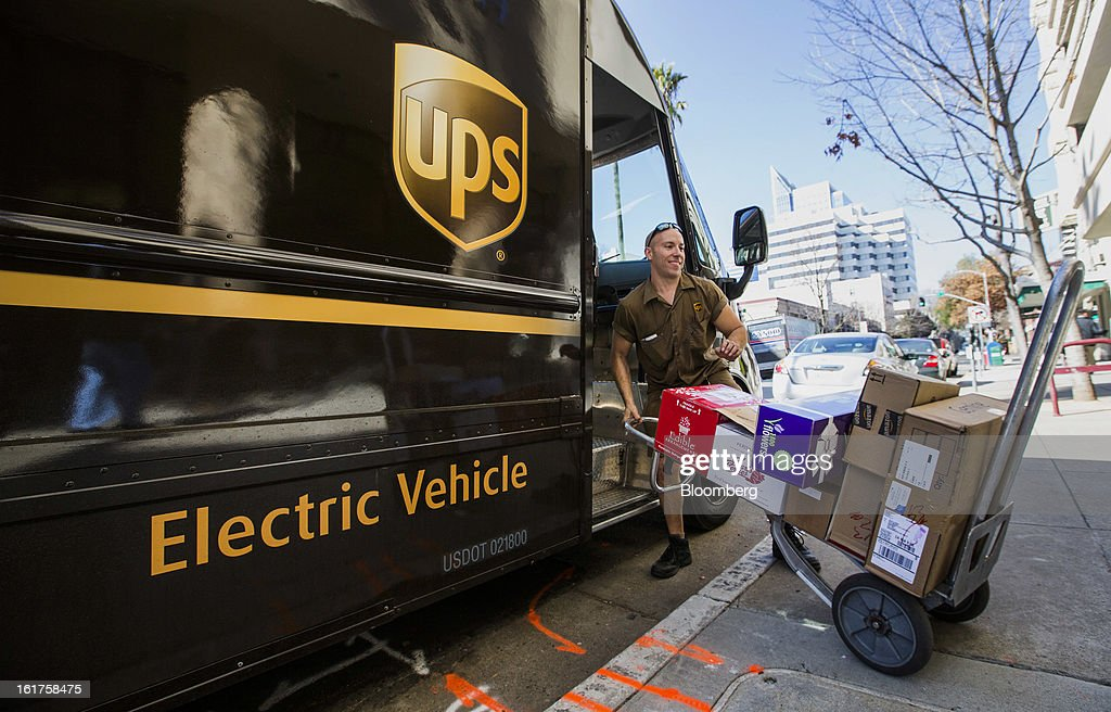 Driver Mike Eastus delivers packages from a United Parcel Service (UPS) all-electric vehicle in Sacramento, California, U.S., on Thursday, Feb. 14, 2013. 100 UPS delivery all-electric vehicles, developed by Electric Vehicles International (EVI), have been deployed this week and are said to eliminate the use of 126,000 gallons of fuel per year. Photographer: Ken James/Bloomberg via Getty Images