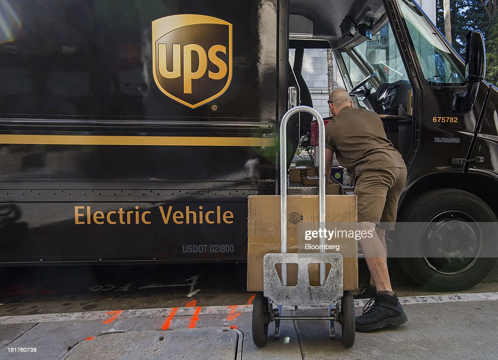 Driver Mike Eastus loads packages to be delivered onto a dolly from a United Parcel Service (UPS) all-electric vehicle in Sacramento, California, U.S., on Thursday, Feb. 14, 2013. 100 UPS delivery all-electric vehicles, developed by Electric Vehicles International (EVI), have been deployed this week and are said to eliminate the use of 126,000 gallons of fuel per year. Photographer: Ken James/Bloomberg via Getty Images