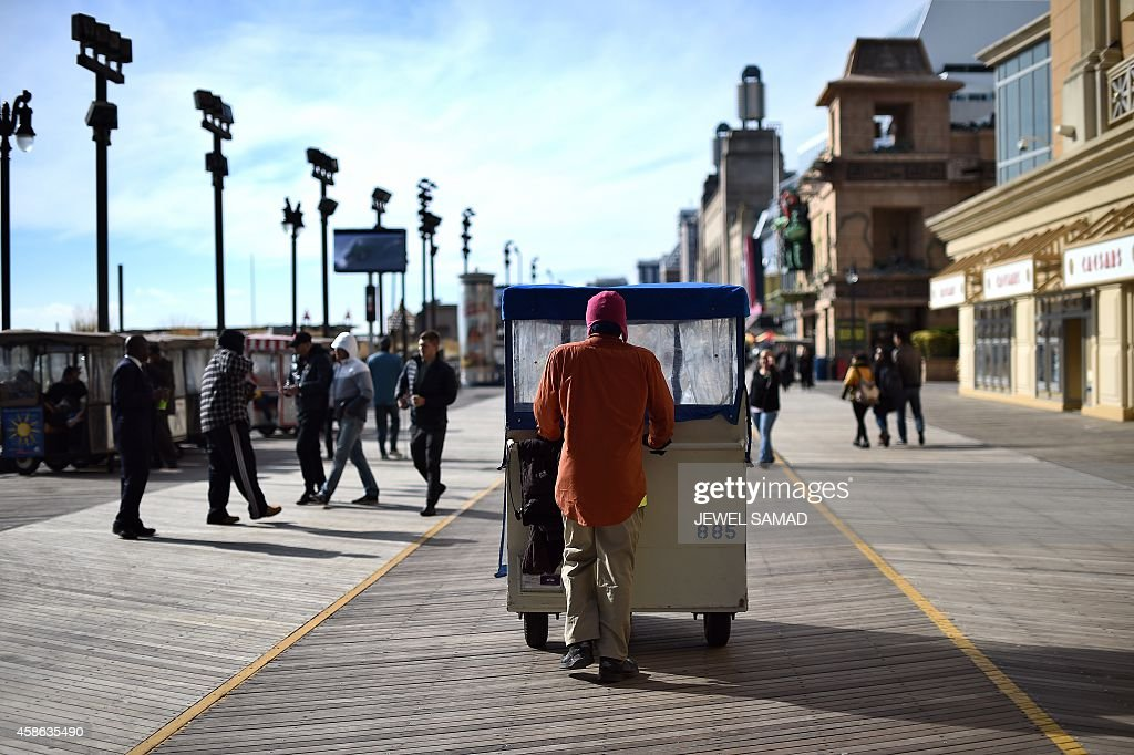 A driver moves his 'push taxi' along the boardwalk in Atlantic City New Jersey on November 8 2014 For decades Atlantic City was a popular vacation...