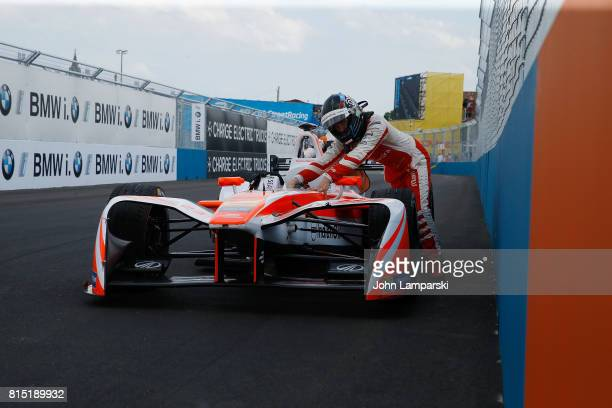 Driver Nick Heidfeld of Machindra Racing pushes his car off the track after it broke an axle during the Formula E Qualcomm New York City ePrix on...