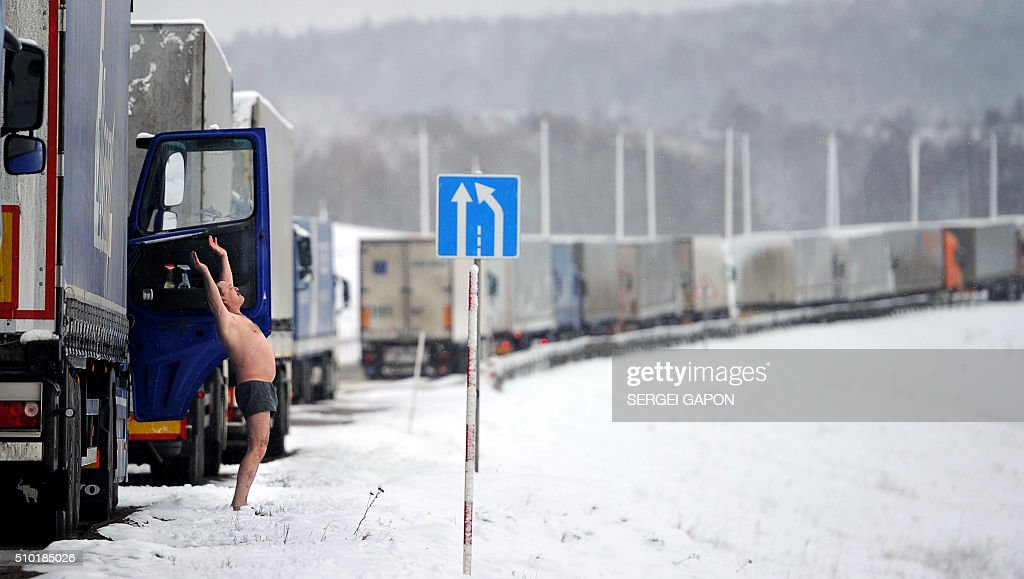 A driver of a trailer truck does his morning exercises as his truck stands in line at the Belarusian-Lithuanian border near the Kamienny Log border point, some 150 km northwest of Minsk, on February 14, 2016. About a hundred Russian trucks wait at the border due to a new road tax imposed on Russian long distance truckers. / AFP / SERGEI GAPON