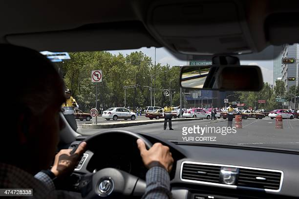 A driver of the private taxi company Uber is diverted by traffic police from Insurgentes Avenue as taxi drivers cross the avenue during a protest...