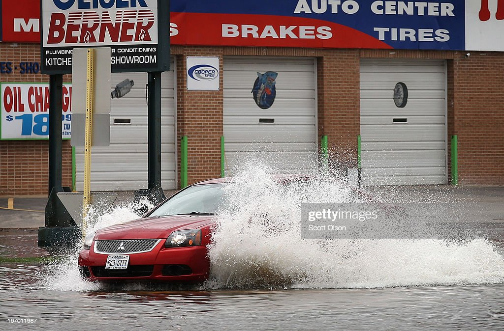 A driver passes through a flooded street on April 19, 2013 in Des Plaines, Illinois. The suburban Chicago town is battling floodwater from the Des Plaines River which is expected to crest at a record 11 feet later today. Record-setting rains and rising rivers have caused wide-spread flooding in many Illinois communities.