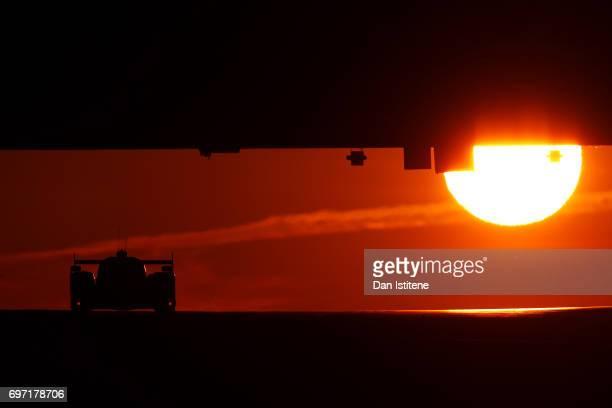 A driver passes under the Dunlop Bridge at sunrise during the Le Mans 24 Hour Race at Circuit de la Sarthe on June 18 2017 in Le Mans France