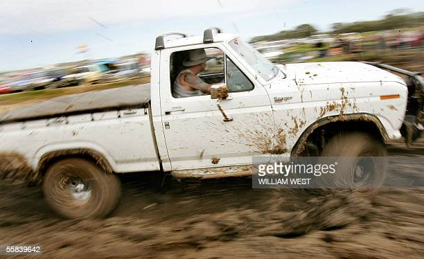 A driver ploughs through the mud as revellers celebrate Australia's affinity of the iconic ute or pickup at the annual Deniliquin Ute Muster which...