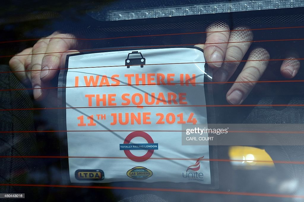 A driver posts a notice in the window of his taxi during a protest by London black cab drivers against a new private taxi service 'Uber', a mobile phone app, in central London on June 11, 2014. Taxi drivers brought parts of London, Paris and other European cities to a standstill on June 11 as they protested against new private cab apps such as Uber which have shaken up the industry. Thousands of London's iconic black cabs, many of them beeping their horns, filled the roads around Buckingham Palace, Trafalgar Square and the Houses of Parliament to the exclusion of any other vehicles.