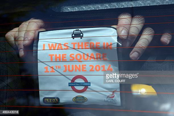 A driver posts a notice in the window of his taxi during a protest by London Black Cab drivers against a new private taxi service 'Uber' a mobile...