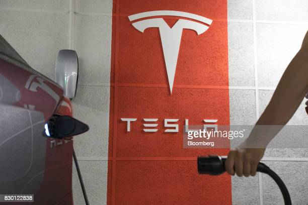 A driver prepares to connect a plug to a Tesla Inc Model X electric automobile at a charging point in a parking lot in Frankfurt Germany on Friday...