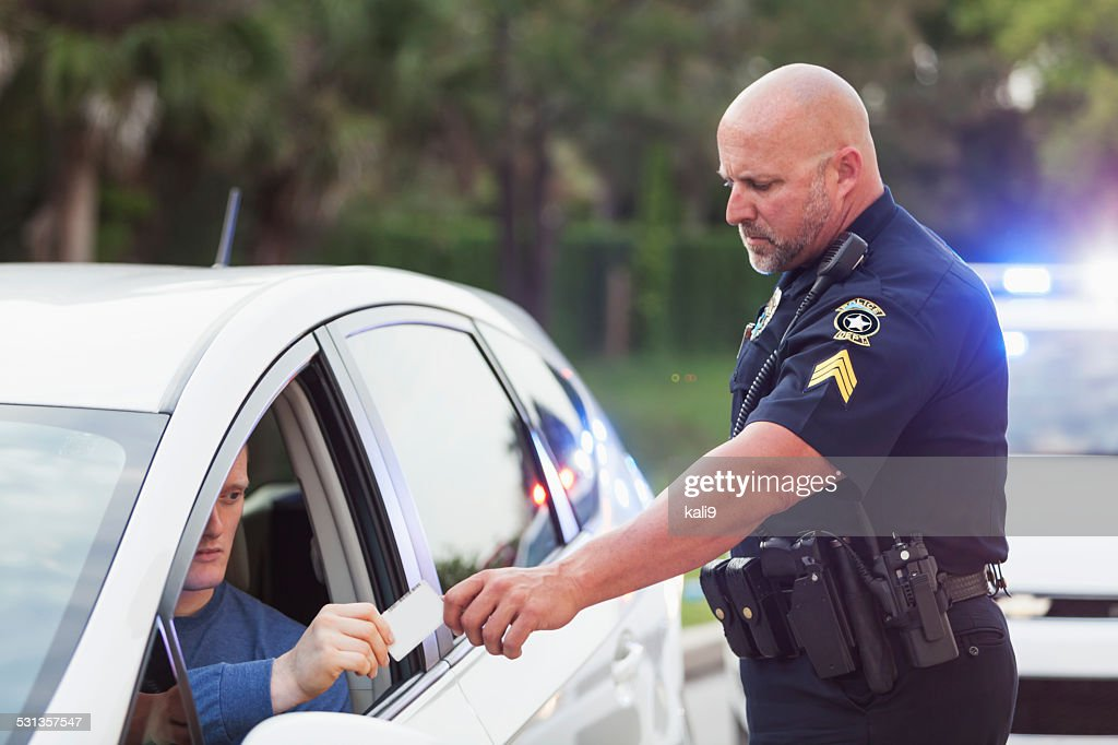 Driver pulled over by police, giving ID to officer : Stock Photo