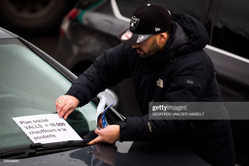 A driver puts a sign on his car that reads, 'Social plan Valls -10,000 drivers to the bin' refering to French Prime Minister Manuel Valls, as VTC vehicles block the roundabout at Place de la Nations to protest against the LOTI law in Paris, on February 9, 2016. Uber and other ride-hailing companies, known in France as 'voitures de tourisme avec chauffeur' (VTC) are a class of companies that allow passengers to book rides with independent professional chauffeurs, / AFP / Geoffroy Van der Hasselt