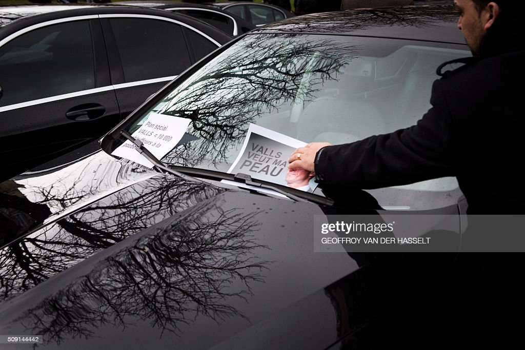 A VTC driver puts a sign on his windshield that reads, 'Valls wants my skin' refering to French Prime Minister Manuel Valls, as VTC vehicles block the roundabout at Place de la Nations to protest against the LOTI law in Paris, on February 9, 2016. Uber and other ride-hailing companies, known in France as 'voitures de tourisme avec chauffeur' (VTC) are a class of companies that allow passengers to book rides with independent professional chauffeurs, / AFP / Geoffroy Van der Hasselt