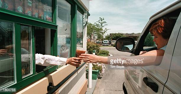 A driver reaches for her coffee order through a window at a driveup Starbucks Coffee shop June 23 2000 in Lombard IL This dualwindow standalone...