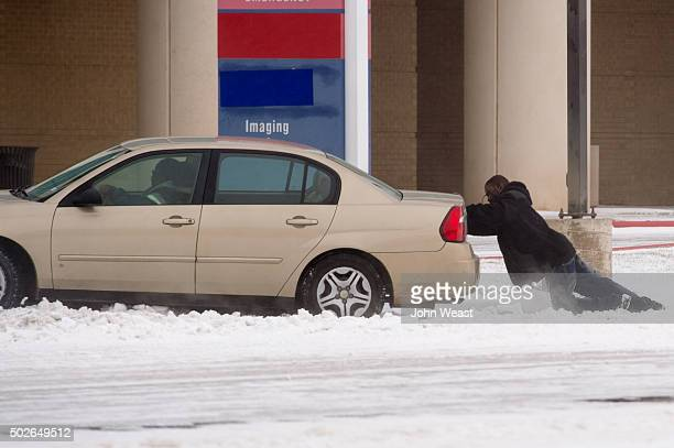 A driver receives a helpful push to escape from a snow drift on December 27 2015 in Lubbock Texas Coming on the heels of several strong tornadoes...