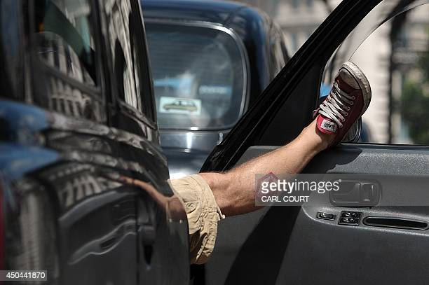 A driver relaxes in his taxi as London Black Cab drivers take part in a protest against a new private taxi service 'Uber' a mobile phone app in...