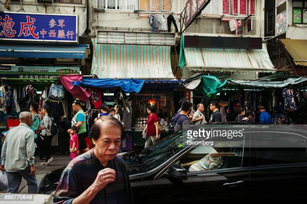 A driver rests inside a BMW AG vehicle as pedestrians walk past street stalls in the Sham Shui Po district of Hong Kong China on Saturday April 29...