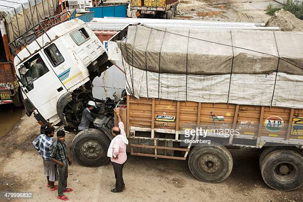 A driver right observes a mechanic performing maintenance on a truck outside the Caravan Roadways Ltd office at Sanjay Gandhi Transport Nagar in...