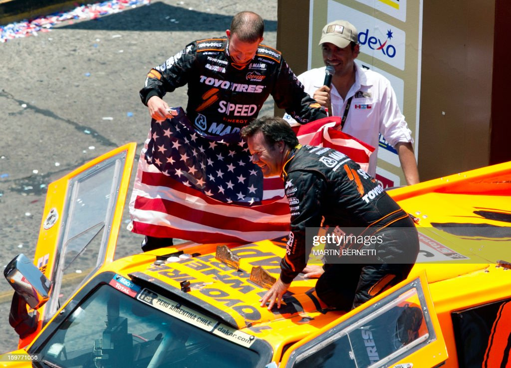 US driver Robby Gordon (R) with co-drivert Kellon Walch (L) arrive at the 2013 Dakar Rally podium ceremony, in Santiago, Chile, on January 20, 2013. Stephane Peterhansel claimed a record fifth Dakar Rally drivers title, and 11th overall of his career, while French compatriot Cyril Despres captured a fifth motorcycling crown.