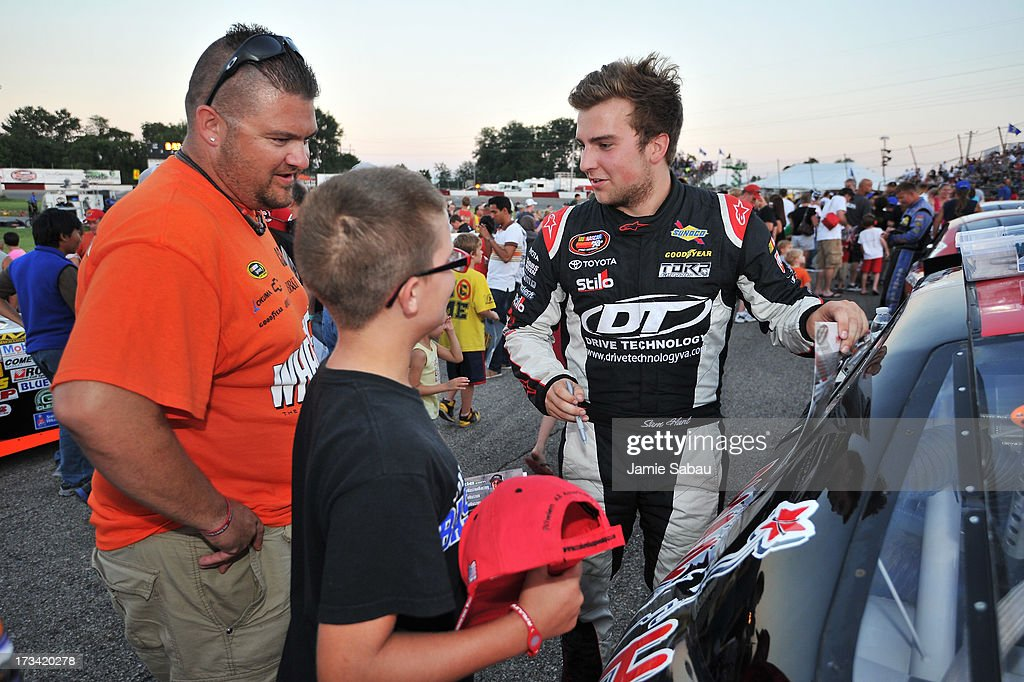 Driver Sam Hunt signs autographs for fans before the start of the NASCAR K&N Pro Series, East NAPA 150 on July 13, 2013 at Columbus Motor Speedway in Columbus, Ohio.