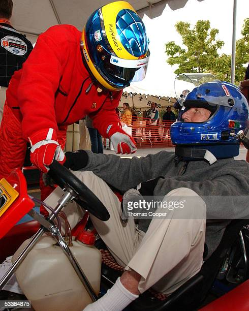 Driver Sebastien Bourdais and actor Paul Newman give each other last minute driving tips before a celebrity gocart race at the Centrix Financial...