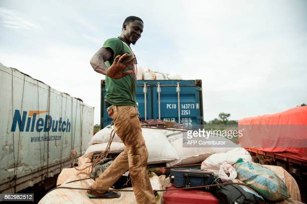 A driver secures the top of his truck that will join a convoy escorted by patrols of the Bangladeshi contingent of the United Nations...