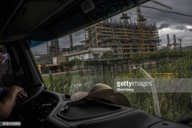 A driver sits in a truck parked in front of the Braskem SA petrochemical plant in Duque de Caxias Brazil on Friday Aug 4 2017 Petroleo Brasileiro SA...