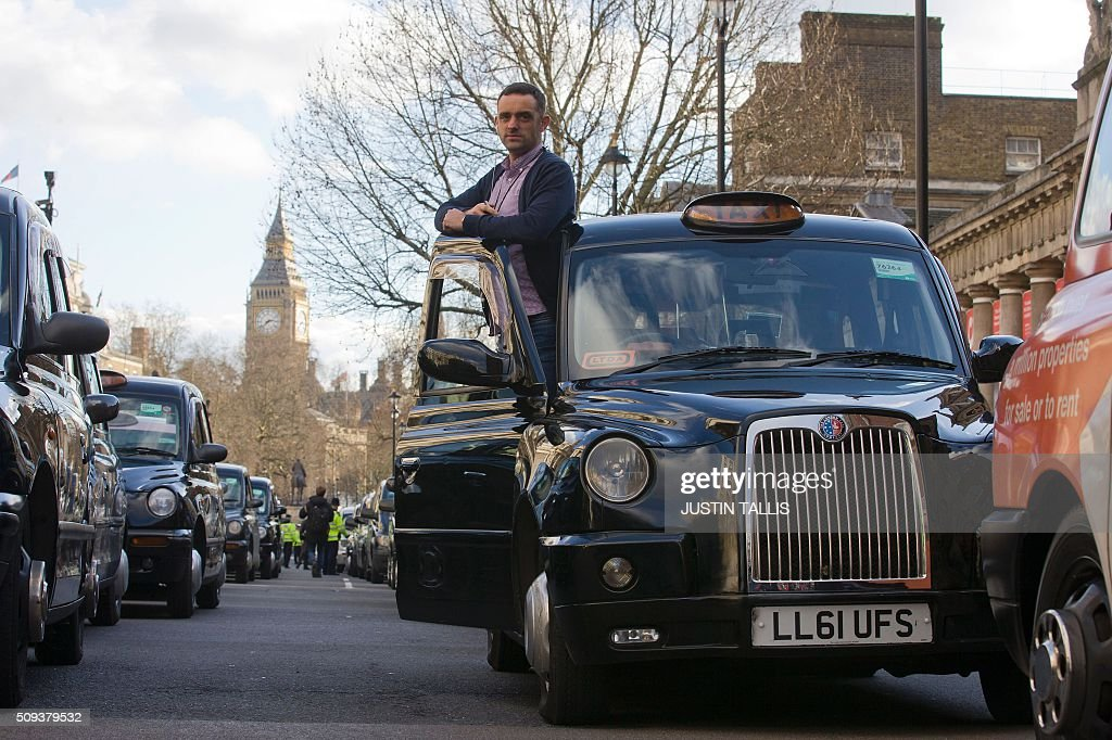 A driver stands by his vehicle as taxi drivers block Whitehall as they demonstrate in central London on February 10, 2016. Up to 5,000 taxi drivers protested in central London over threats to passenger safety and deregulation / AFP / JUSTIN TALLIS