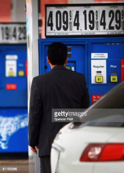A driver stands in front of a pump before fueling up his car at a gas station where prices have gone over $4 per gallon May 19 2008 in Douglaston in...