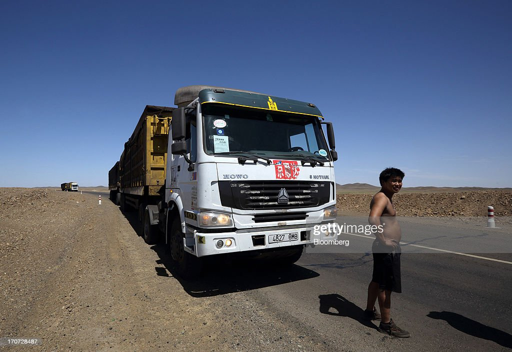 A driver stands in front of his truck which is carrying coal to a reloading facility on the border with China, in South Gobi, Mongolia, on Thursday, June 6, 2013. Mongolia, a country of almost 2.9 million people, has some of the world's biggest undeveloped mineral reserves, including Oyu Tolgoi, a copper and gold mine, and Tavan Tolgoi, a coal deposit. Photographer: Tomohiro Ohsumi/Bloomberg via Getty Images