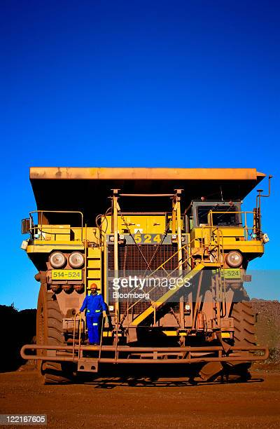 A driver stands on the access steps of a Komatsu Ltd haul truck at Sishen open cast mine operated by Kumba Iron Ore Ltd an iron oreproducing unit of...