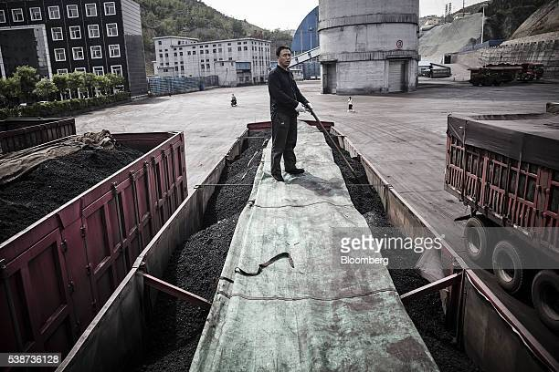 A driver stands on top of a tarp covering a truck filled with coal at a coal mine and processing facility in Liulin Shanxi province China on Thursday...