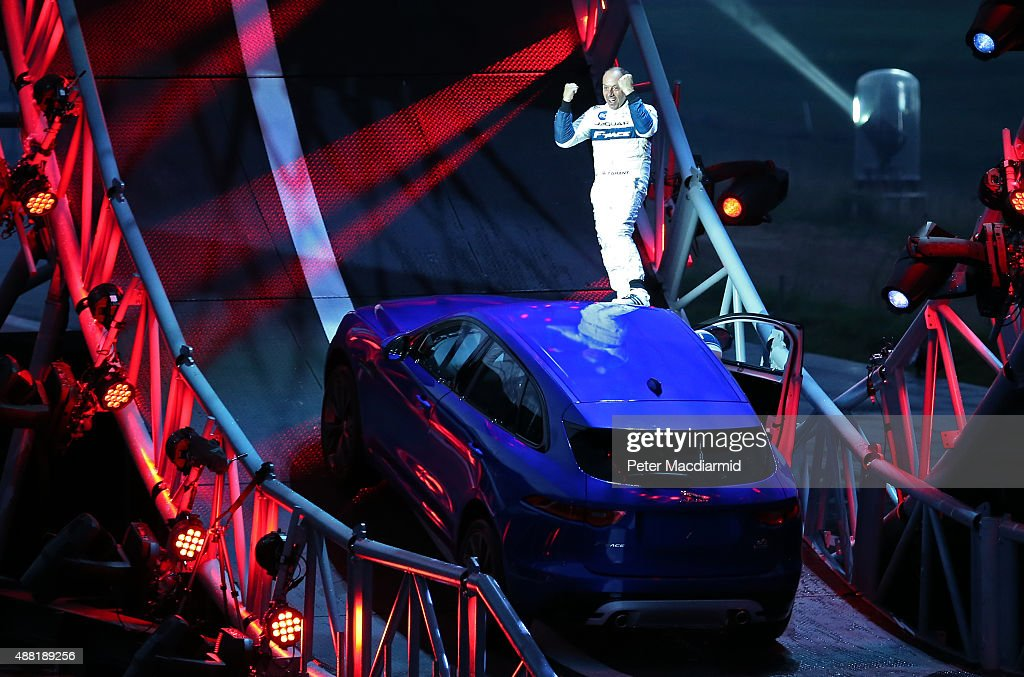 Driver Terry Grant stands on a Jaguar FPACE after he drove round a giant loop the loop track on September 14 2015 in Frankfurt Germany Jaguar is...