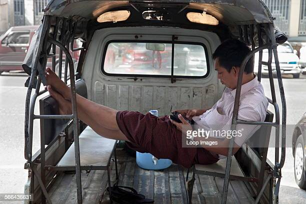 A driver texting in the back of his public transport pickup in Yangon in Myanmar