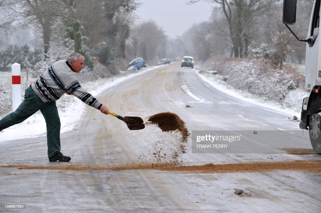 A driver throws sand near the tires of his truck on a ice covered road on January 18, 2013 near Vigneux-de-Bretagne, Brittany, western France. Thirty-seven French departments are under medium range (orange) alert due to the inclement weather. AFP PHOTO FRANK PERRY