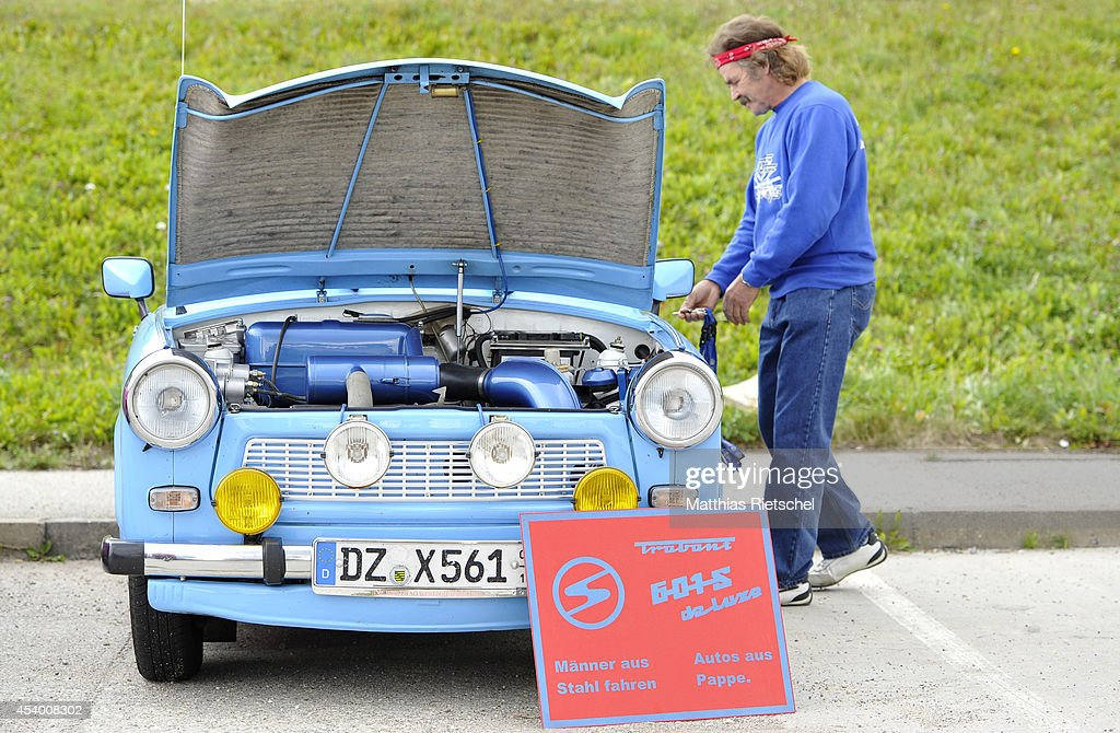A driver unlocks his Trabant 601 car, the sign in front of the car reads: Men made from steel drive cars made from cardboard, as fans of the East German Trabant car gather for their 7th annual get-together on August 23, 2014 in Zwickau, Germany. Hundreds of Trabant enthusiasts arrived to spend the weekend admiring each others cars, trading stories and enjoying activities. The Trabant, dinky and small by modern standards, was the iconic car produced in former communist East Germany and today has a strong cult following.