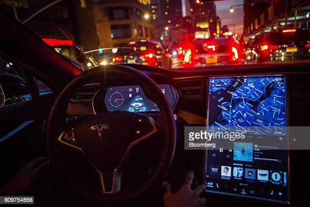 A driver uses map navigation and entertainment features on a touchscreen control panel with the Tesla Motors Inc 80 software update inside a Model S...
