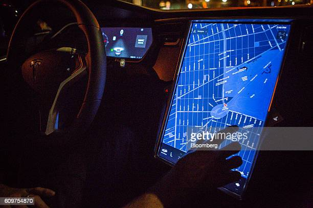 A driver uses the map navigation feature on a touchscreen control panel with the Tesla Motors Inc 80 software update inside a Model S P90D vehicle in...