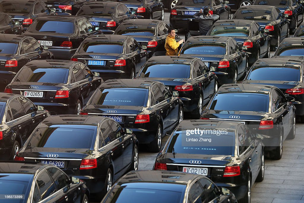 A driver waits amongst official cars, parked outside the Great Hall of the People, during the closing session of the 18th National Congress of the Communist Party of China (CPC) at the Great Hall of the People on November 14, 2012 in Beijing, China. Members of the Standing Committee of the Political Bureau of the new CPC Central Committee will meet with journalists on November 15, 2012.