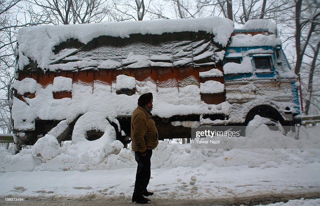 A driver waits out of his truck on highway after his vehicle carrying essential supply skidded off the road amid heavy snowfall on December 14, 2012, in Banihal, 110 km (68 miles) south of Srinagar, the summer capital of Indian Administered Kashmir, India. Most parts of the Kashmir Valley, including Srinagar, received fresh snowfall, leading to closure of the 300 km (188 miles) Jammu-Srinagar Highway, the only road link between Kashmir and rest of India. Project Beacon authorities of the Border Roads Organisation, that maintains the highway, had already started efforts to clear the highway for traffic. The number of vehicles stranded on the highway was being ascertained.