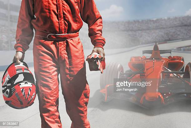 Driver walking away from Formula One race car.