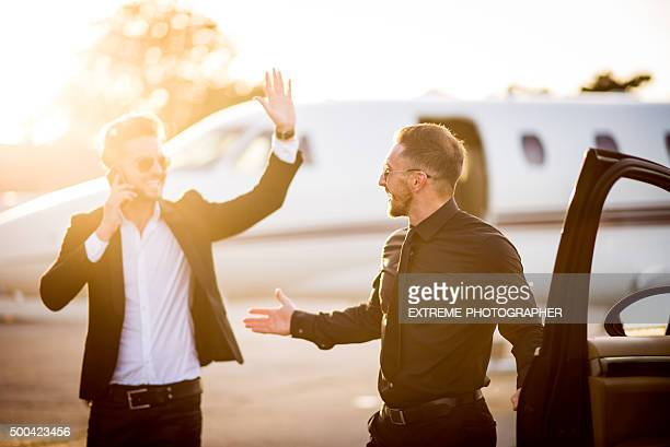 Driver with car welcoming celebrity at the airport