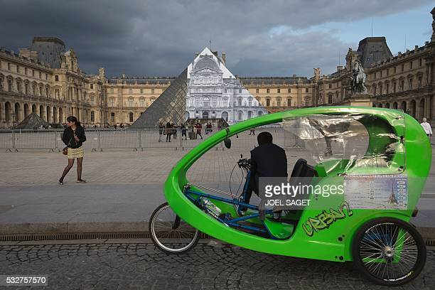 A driver with his cycle rickshaw stands in front of the Louvre Pyramid covered with a giant photograph of the museum by French artist and...
