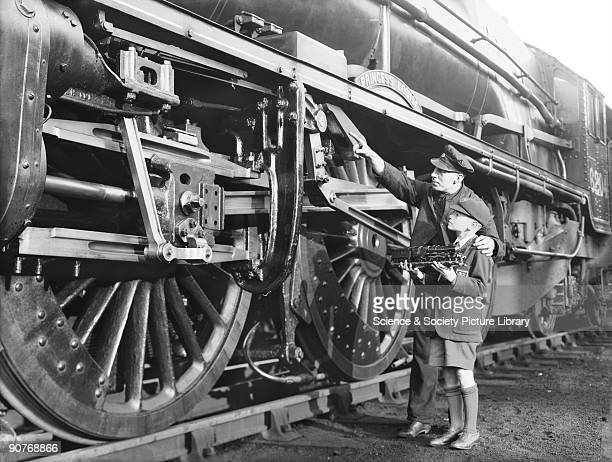 Driver with the 'Princess Royal' class 462 locomotive number 6204 Princess Louise 1938 The driver is with a young boy holding a model locomotive of...