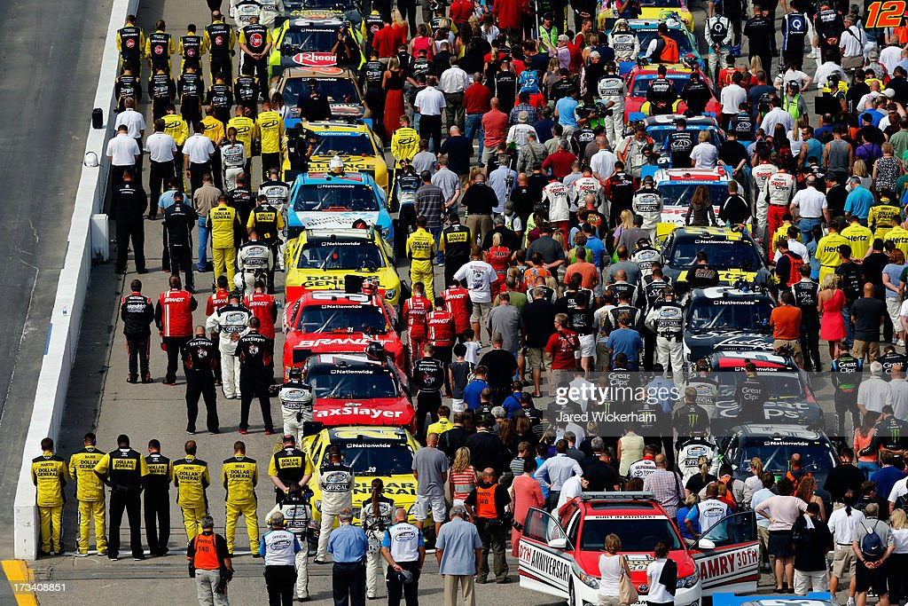 Drivers and crew members stand on the grid during the national anthem prior to the NASCAR Nationwide Series CNBC Prime's The Profit 200 at New Hampshire Motor Speedway on July 13, 2013 in Loudon, New Hampshire.