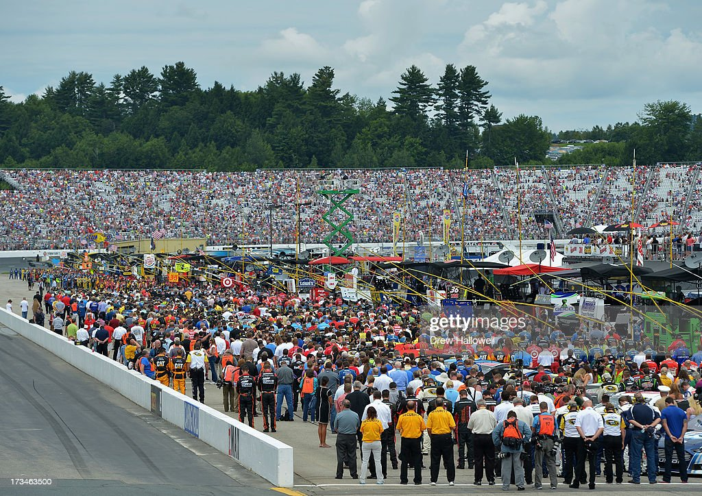 Drivers and crew members stand on the grid for the national anthem before the NASCAR Sprint Cup Series Camping World RV Sales 301 at New Hampshire Motor Speedway on July 14, 2013 in Loudon, New Hampshire.