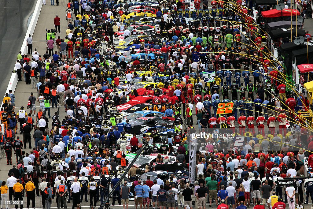 Drivers and crews stand during the playing of the National Anthem at the New Hampshire Motor Speedway Camping World RV Sales 301.