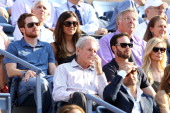 NASCAR drivers Brian Vickers and Jimmie Johnson along with Johnson's wife Chandra sit behind actor Stanley Tucci as they watch Rafael Nadal of Spain...