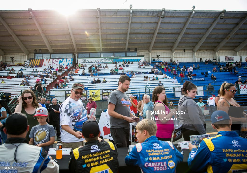 Drivers, including Derek Kraus #19, third from left, sign autographs for fans before the NASCAR K&N Pro Series West NAPA Auto Parts 150 on August 12, 2017 at Evergreen Speedway in Monroe, Washington.